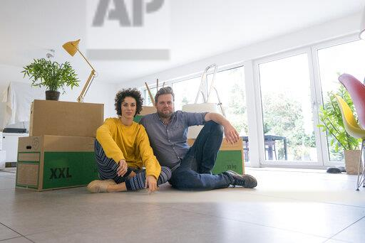 Portrait of couple sitting in living room with cardboard boxes