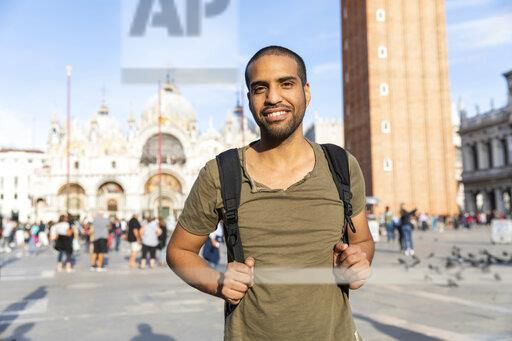 Italy, Venice, portrait of smiling young man on St Mark's Square