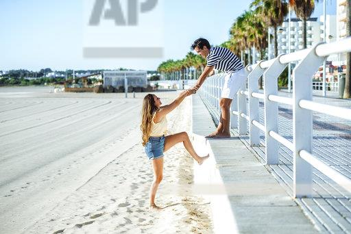 Man helping woman to climb up from the beach to the promenade
