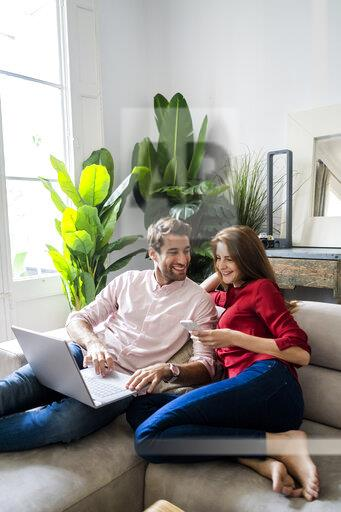 Man and woman sitting on couch, working on laptop, using smartphone