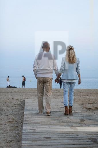 Spain, Barcelona, rear view of senior couple walking hand in hand on the beach at dusk