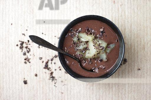 Chocolate pudding with pineapple chunks and cacao nibs