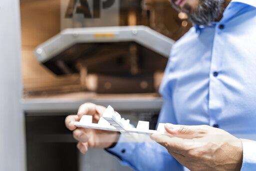 Close-up of man holding workpiece at 3d printer
