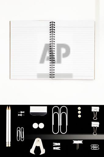 White office utensils on black background and notepad on whilte background