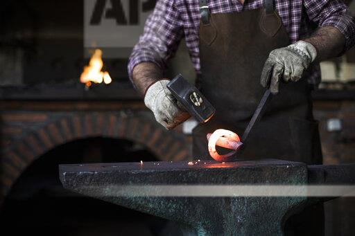 Close-up of blacksmith working with hammer at anvil in his workshop