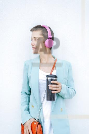 Woman dressed in jacket with thermo mug and pink headphones