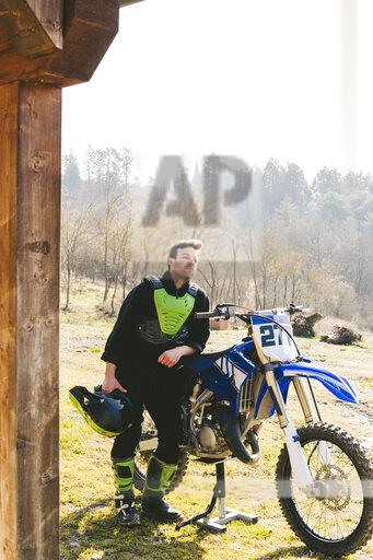 Motocross driver with jacked up motorbike