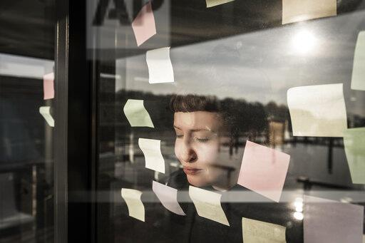 Tired woman leaning against window pane with sticky notes