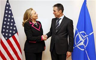 U.S. Secretary of State Hillary Clinton shakes hands with NATO Secretary-General Anders Fogh Rasmussen at the NATO headquarters in Brussels