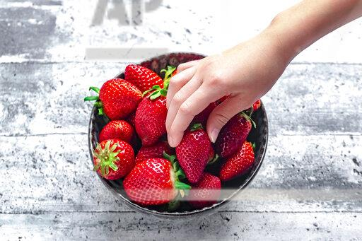 Bowl with fresh strawberries, hand of a girl