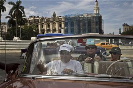 Tourists sit in a classic American car in Old Havana, Cuba, Friday, Sept. 26, 2014. Tourism is one of Cuba's top four generators of income, along with nickel mining, medical services and remittances from relatives living abroad.