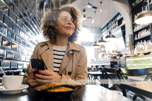 Smiling woman with cell phone in a cafe