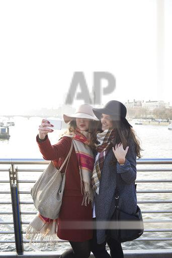 UK, London, two women taking a selfie on Millennium Bridge with cityscape in background