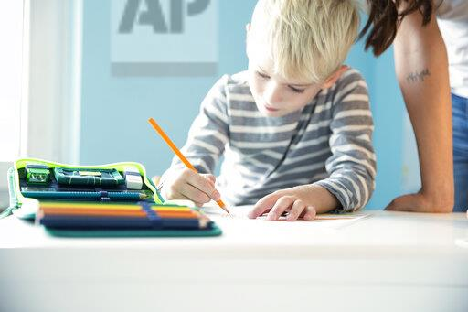 Boy doing homework with mother leaning on desk