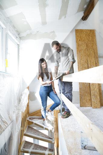 Couple in attic to be renovated looking in catalgue