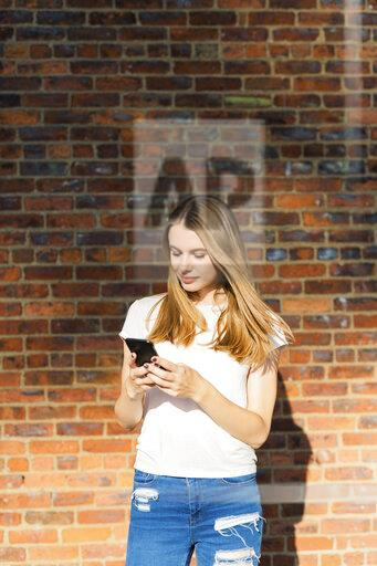 Young woman in front of brick wall, using smartphone