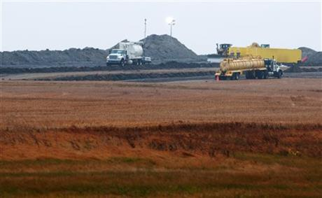 """In this Oct. 11, 2013 file photo, cleanup continues at the site of an oil pipeline leak and spill north of Tioga, N.D. North Dakota, the nation's No. 2 oil producer behind Texas, recorded nearly 300 oil pipeline spills in less than two years, state documents show. None of them were reported to the public. According to records obtained by The Associated Press, the pipeline spills, many of them small, are among some 750 """"oil field incidents"""" that have occurred since January 2012 without public notification. (AP Photo/Kevin Cederstrom, File)  Click to enlarge."""