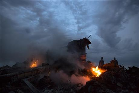 People walk amongst the debris at the crash site of a passenger plane near the village of Hrabove, Ukraine, Thursday, July 17, 2014