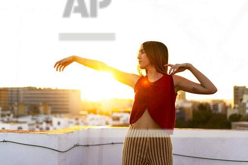 Gracious teenage girl moving on roof terrace in the city at sunset