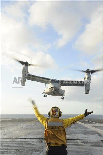 Creative AP Photo/Stocktrek Images A Military   vertical Aviation Boatswain's Mate signals an MV-22 Osprey to land.