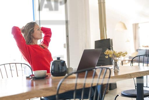 Woman with laptop on dining table at home having a break