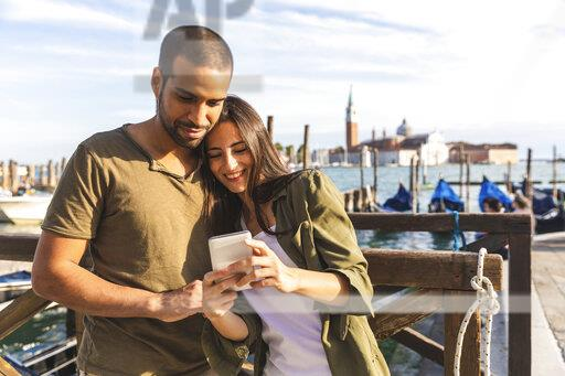 Italy, Venice, affectionate young couple with cell phone and gondola boats in background
