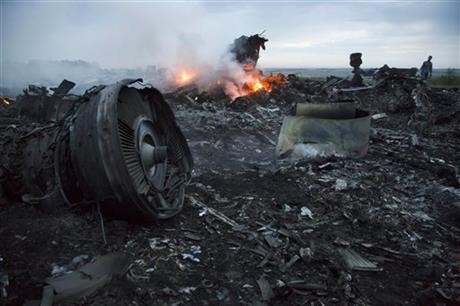 A man walks amongst the debris at the crash site of a passenger plane near the village of Hrabove, Ukraine, Thursday, July 17, 2014.
