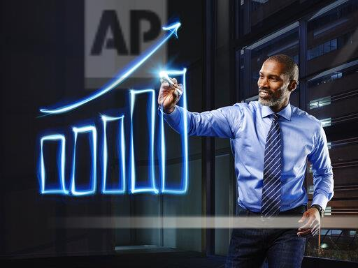Businessman painting upturning bar chart with light