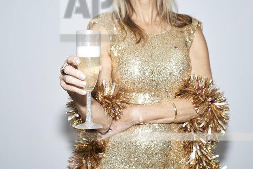 Senior woman wearing golden dress, celebtraing New Year's Eve, mid section