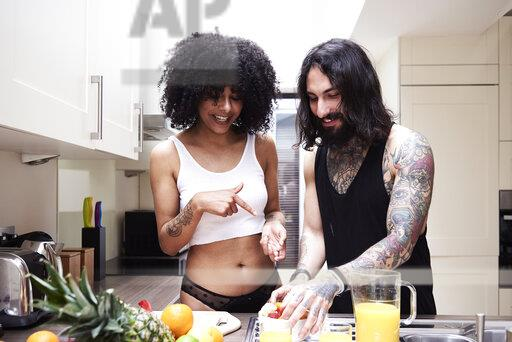 Happy young couple preparing healthy meal in kitchen