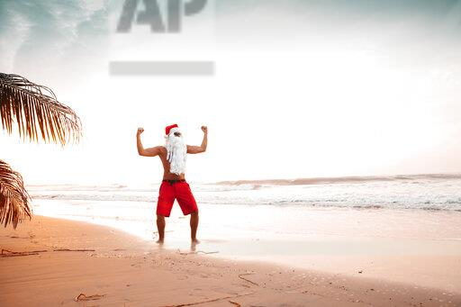 Thailand, man dressed up as Santa Claus posing on the beach at sunset