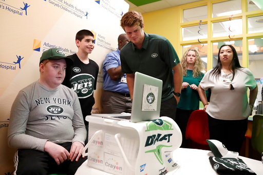 Raymond Schwartz, 14, left, of Cranford, N.J., talks on a video conference call as New York Jets quarterback Sam Darnold, center, who was drafted No. 3 overall in Thursday's NFL football draft, looks on during a visit to the Goryeb Children's Hospital, Saturday, April 28, 2018, in Morristown, N.J. (AP Photo/Julio Cortez)