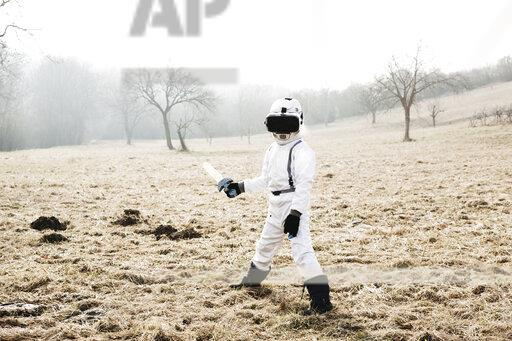 Boy wearing white space suit with sword pon on a meadow with virtual reality glasses