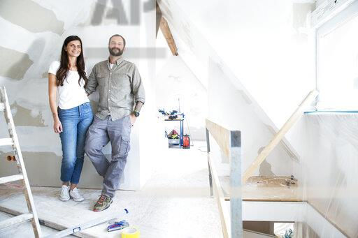 Portrait of confident couple standing in attic to be renovated