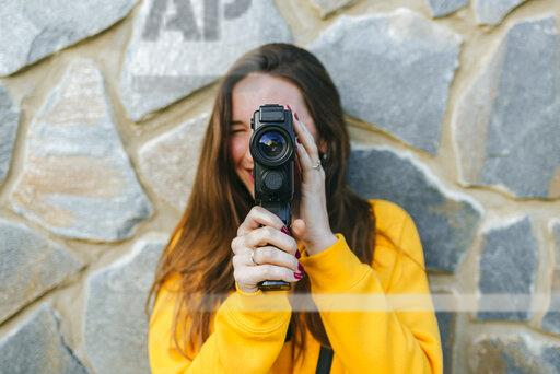 Young woman with vintage camera at a stone wall