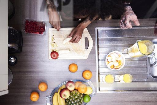 Top view of couple cutting fruit in kitchen
