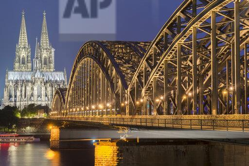 Germany, Cologne, view to lighted Cologne Cathedral with Hohenzollern Bridge in the foreground