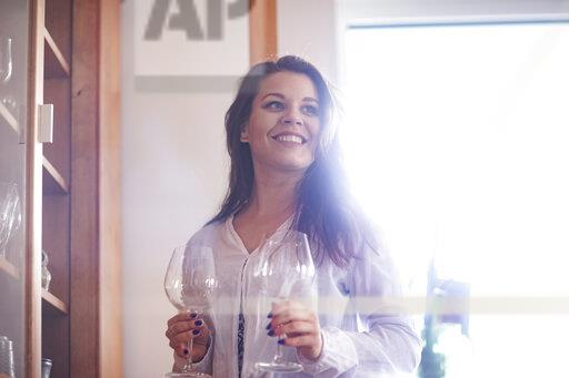 Portrait of smiling young woman with two empty red wine glasses at home