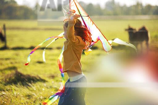 Redheaded girl in field with kite