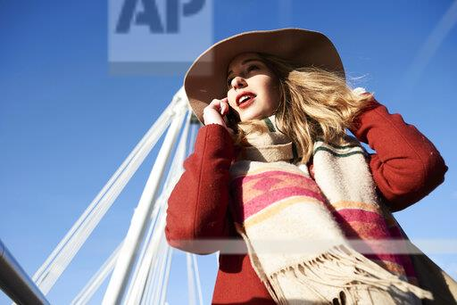 UK, London, stylish young woman talking on cell phone on Millennium Bridge
