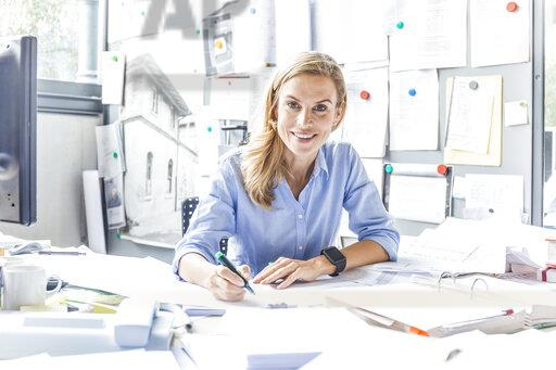Portrait of smiling woman doing paperwork at desk in office