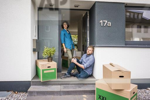 Couple at house entrance with cardboard boxes