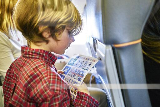 Boy sitting on an airplane reading safety instructions