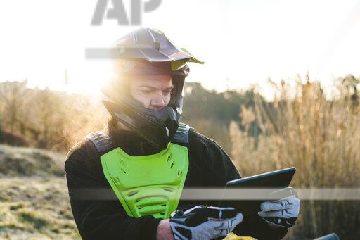 Portrait of motocross driver looking at tablet at sunset