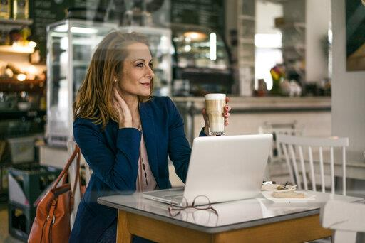 Businesswoman sitting in coffee shop, having lunch, working on laptop