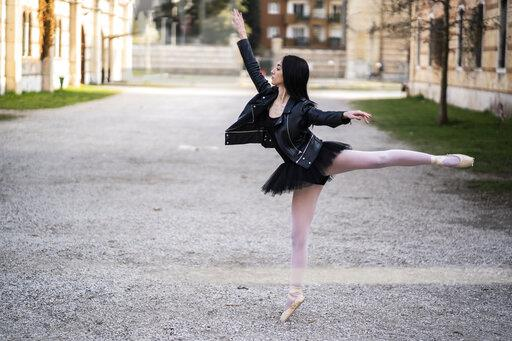Italy, Verona, Ballerina dancing in the city wearing leather jacket and tutu