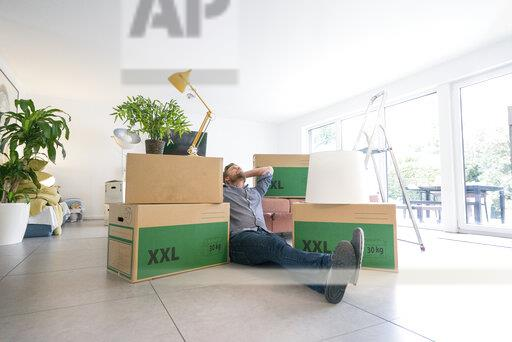 Man sitting on the floor in living room surrounded by cardboard boxes