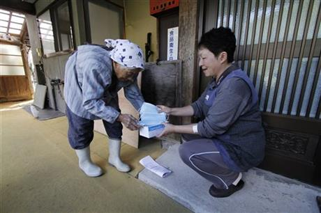 Yaeko Arai, left, 85, delivers a box of surgical masks to her neighbor Emiko Miura, 53, as Mount Ontake continues to erupt in Otaki in Nagano Prefecture, central Japan, Wednesday, Oct. 1, 2014. Arai spent the afternoon handing a box of masks to each household as the village distributed more than 400 boxes of masks to 9 districts as a precaution for ash that may fall if eruptions worsen. The Japan Meteorological Agency said levels of toxic gases were too low to cause health problems in distant towns, but cautioned residents that ash could cause eye irritation, particularly among contact lens users, or trigger asthmatic symptoms. (AP Photo/Koji Ueda)
