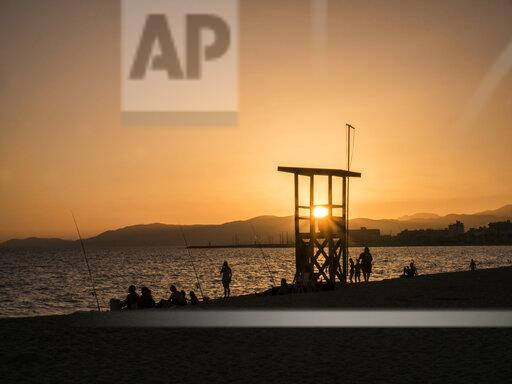 Spain, Mallorca, Silhouettes of people relaxing on Playa de Palma at sunset