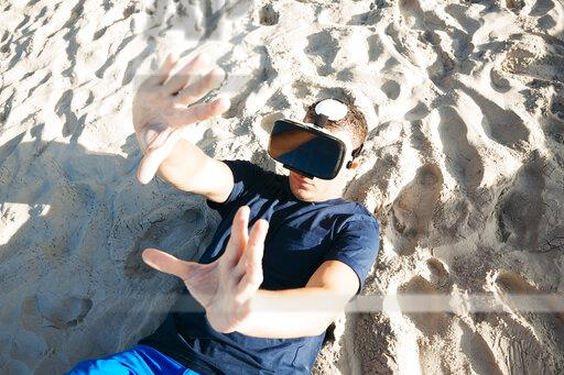 Man wearing VR glasses lying in sand on the beach